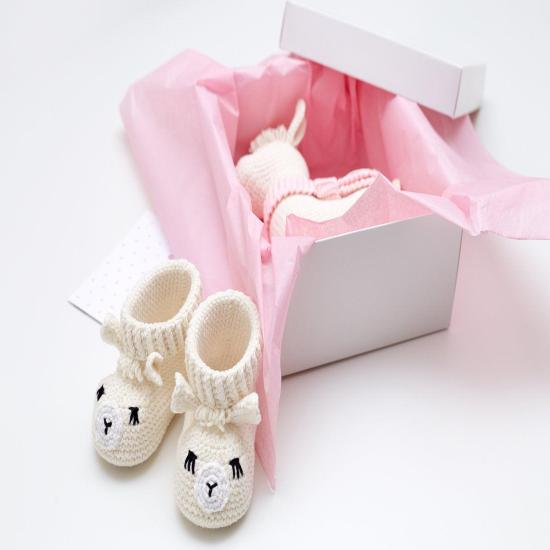 Baby girl sprinkle shower reveal party gift box with cute crochet llama toy and sweet newborn animal booties Unique pregnancy present basket